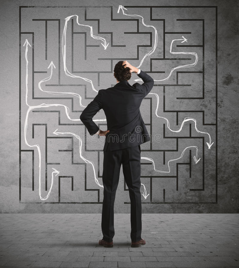 Businessman seek the solution. Confused business man seeks a solution to the labyrinth drawn on the wall royalty free stock images
