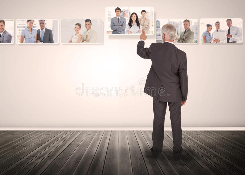 Businessman selecting business people digital interface. Among group of pictures stock image