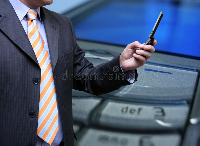Businessman sending a mms. From his cellphone royalty free stock photo