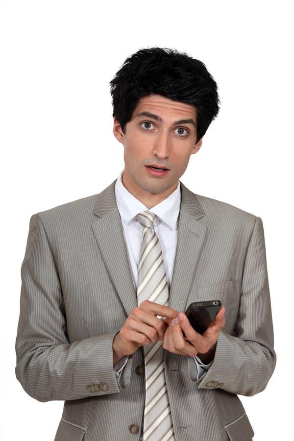 Businessman sending a text message. Wide-eyed businessman sending a text message royalty free stock photos