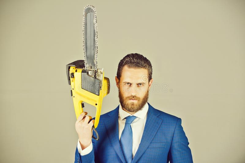 Businessman or serious bearded man hold yellow chainsaw in outfit. Businessman or serious bearded man hold yellow chainsaw in formal outfit on grey background stock images