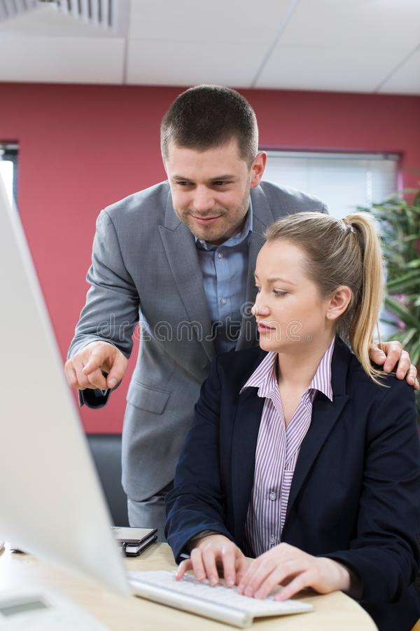 Businessman Sexually Harassing Female Colleague In Office royalty free stock photo
