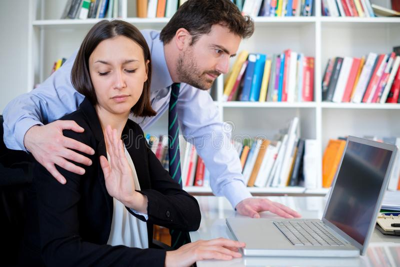 Businessman sexually Harassing a young female colleague. Sexual harassment in workplace. Unhappy female employee feeling disgusted stock photography