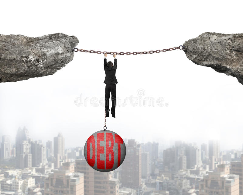 Businessman shackled by debt ball hanging on chains connected cl. Businessman shackled by debt concrete ball hanging on iron chains connected two cliffs with stock photo