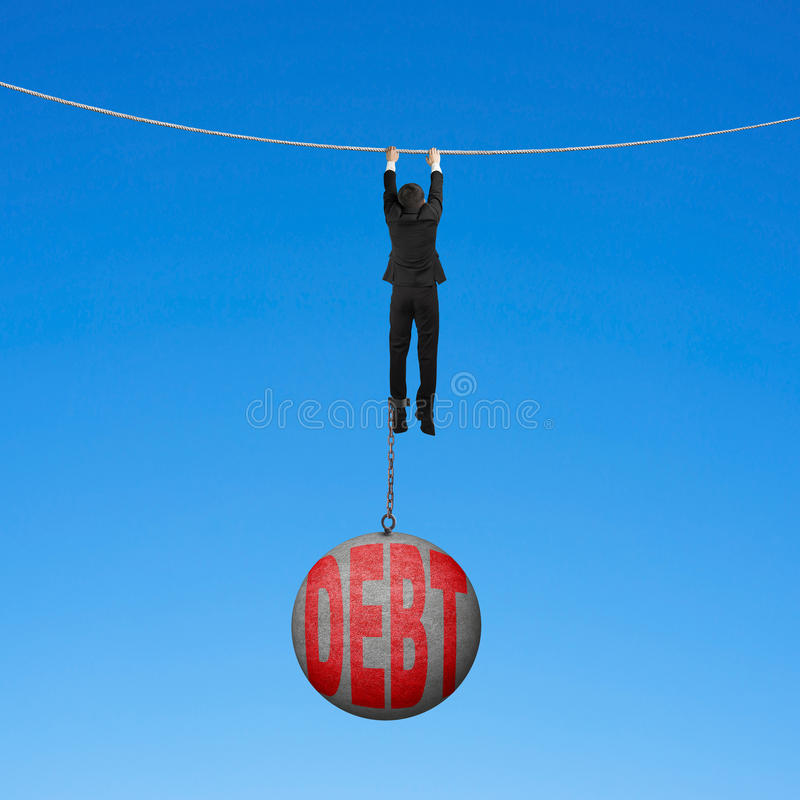 Businessman shackled by debt ball hanging on rope blue background. Businessman shackled by debt concrete ball hanging on the rope with blue background stock photo