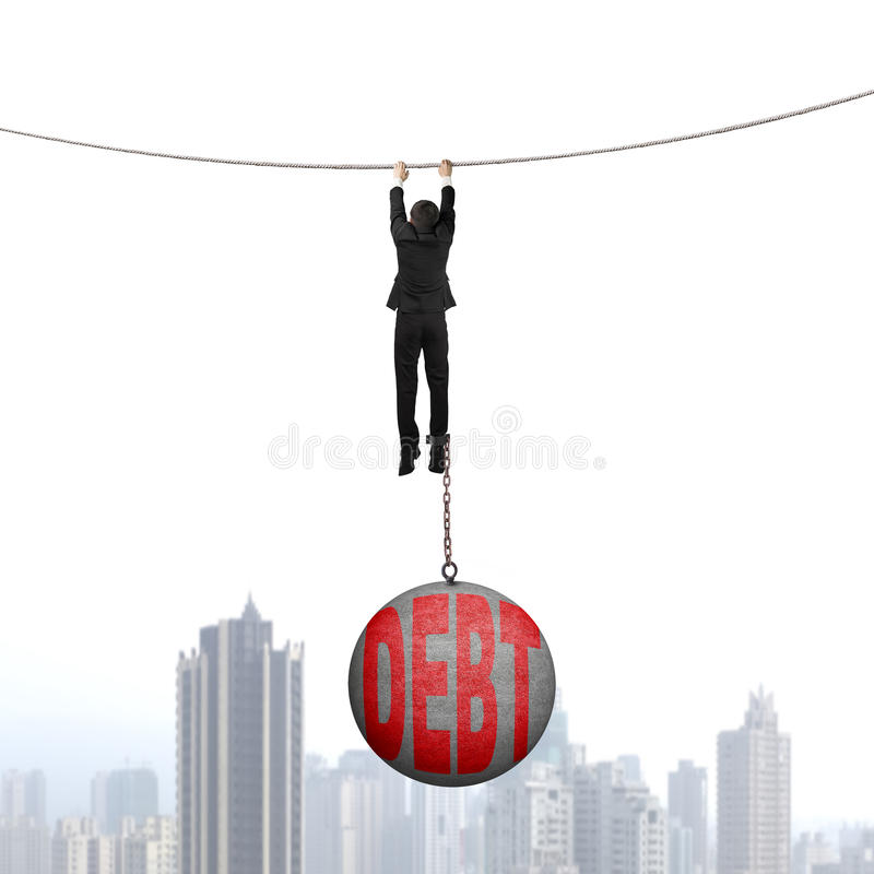 Businessman shackled by debt ball hanging on rope with cityscape. Businessman shackled by debt concrete ball hanging on the rope with urban scene background royalty free stock photos