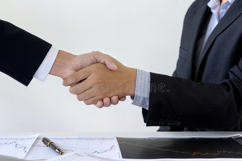 businessman shake hand at the office table between computer royalty free stock photo