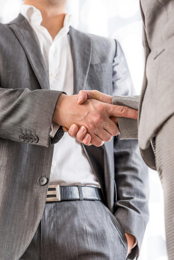 Businessman shaking hands with a client. Relaxed confident businessman with his one hand in his pocket standing shaking hands with a client in greeting stock photography