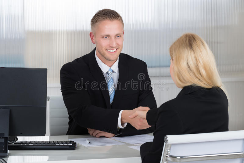 Businessman Shaking Hands With Female Candidate At Desk stock photography