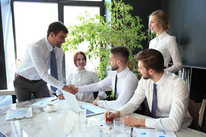 Businessman shaking hands to seal a deal with his partner and colleagues in office royalty free stock image