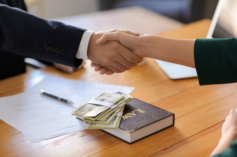 Businessman shaking hands with woman after bribery, closeup. Corruption concept stock images