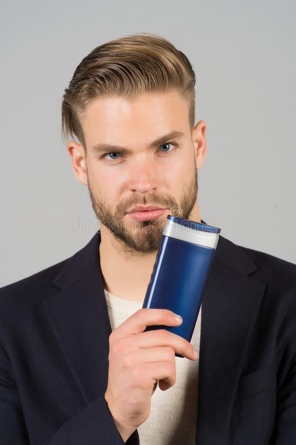 Businessman with shampoo bottle. Bearded man hold gel tube. Hair care and skincare. Morning grooming at hairdresser. Salon or barbershop. Health and healthcare royalty free stock photography