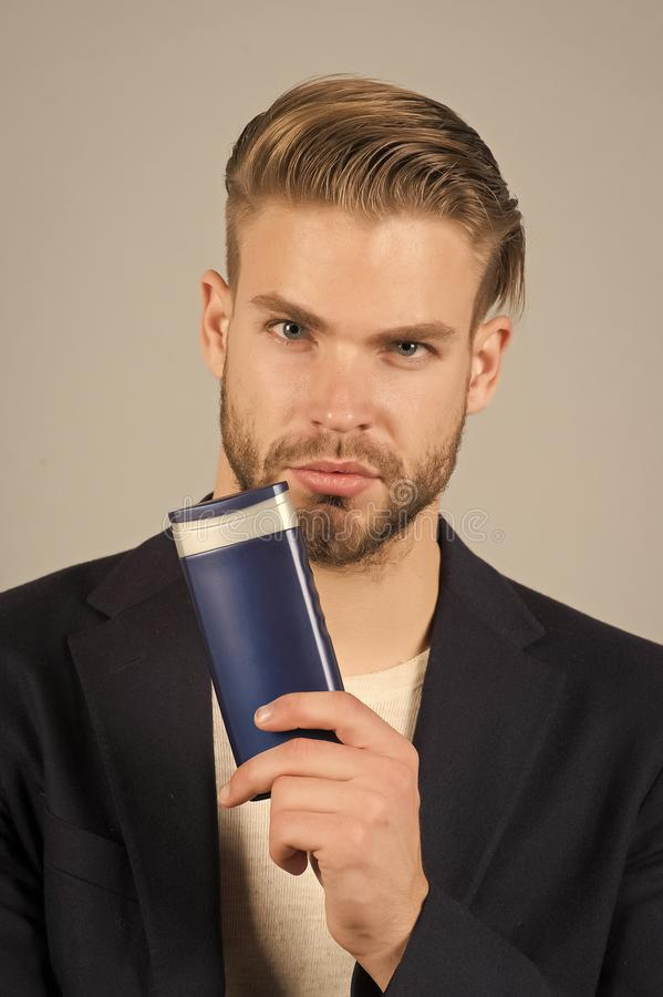 Businessman with shampoo bottle. Bearded man hold gel tube. Hair care and skincare. Morning grooming at hairdresser. Salon or barbershop. Health and healthcare stock image