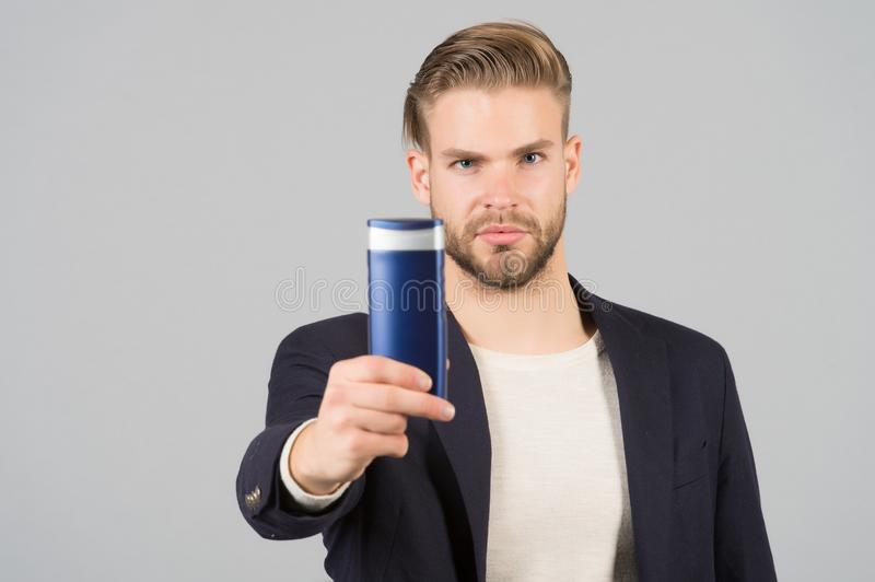Businessman with shampoo or gel bottle in hand. Bearded man with stylish hair or haircut. Cosmetic for spa bath or shower. Hair ca. Re and beard grooming. Mens royalty free stock photo