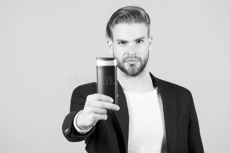 Businessman with shampoo or gel bottle in hand. Bearded man with stylish hair or haircut. Cosmetic for spa bath or. Shower. Hair care and beard grooming. Mens stock photo