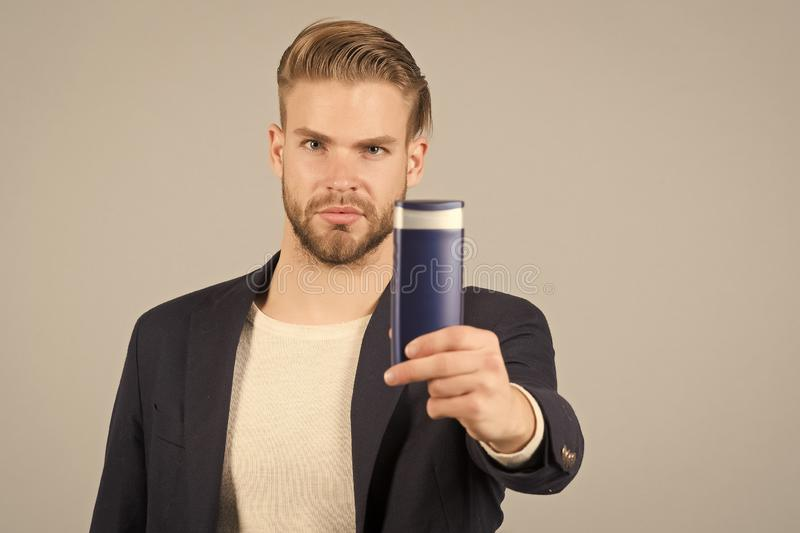 Businessman with shampoo or gel bottle in hand. Bearded man with stylish hair or haircut. Cosmetic for spa bath or. Shower. Hair care and beard grooming. Mens royalty free stock photo