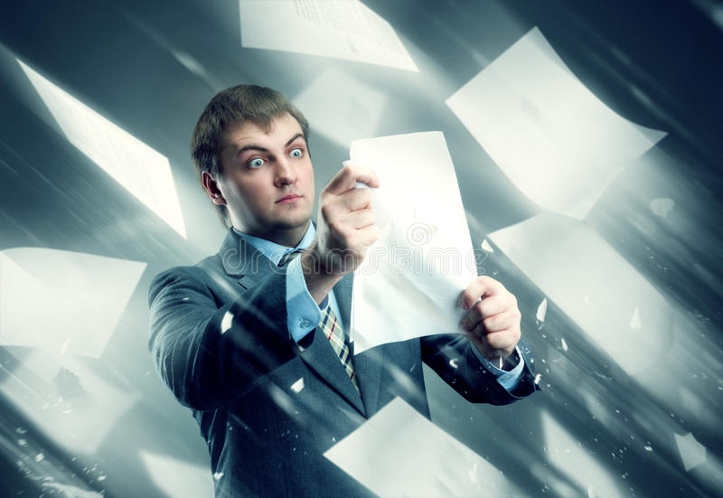 Businessman with sheets of white papers stock images