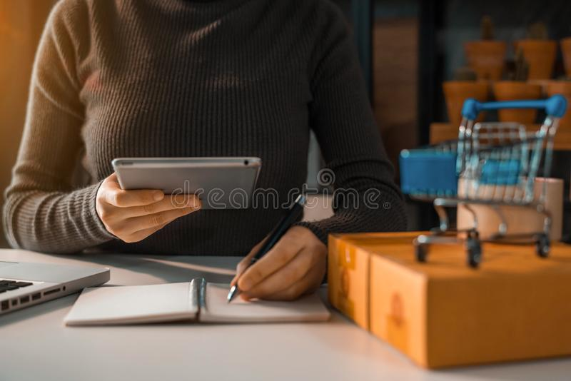 Businessman shipping shopping online. Shipping shopping online ,woman start up small business owner writing address on cardboard box at workplace.small business stock photography