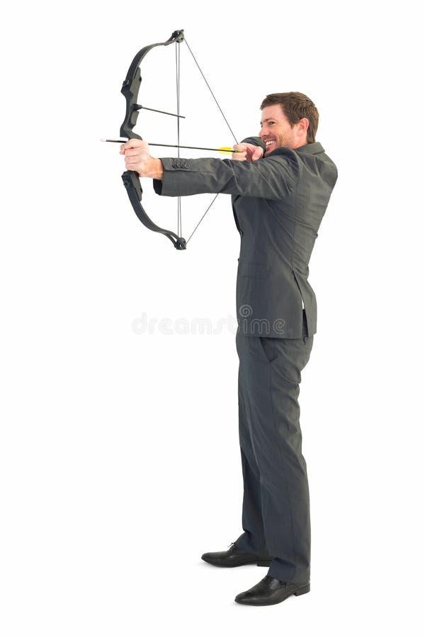 Businessman shooting a bow and arrow royalty free stock photos