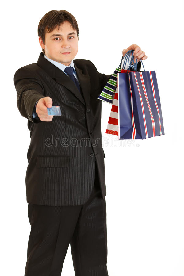 Businessman with shopping bags giving credit card royalty free stock photography
