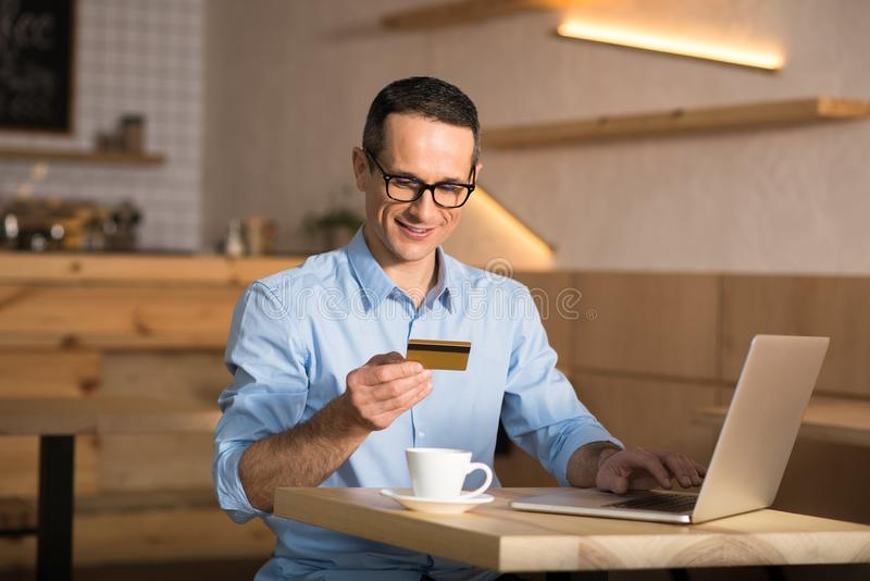 Businessman shopping online with credit card. Handsome businessman shopping online with credit card using laptop in cafe royalty free stock photos