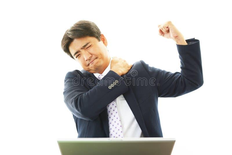 Businessman with shoulder pain. stock photos