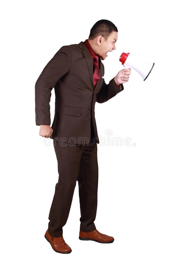Businessman Shout with Megaphone. Young Asian businessman wearing brown formal suit shout with megaphone, angry big boss giving instruction, side view full body royalty free stock photo