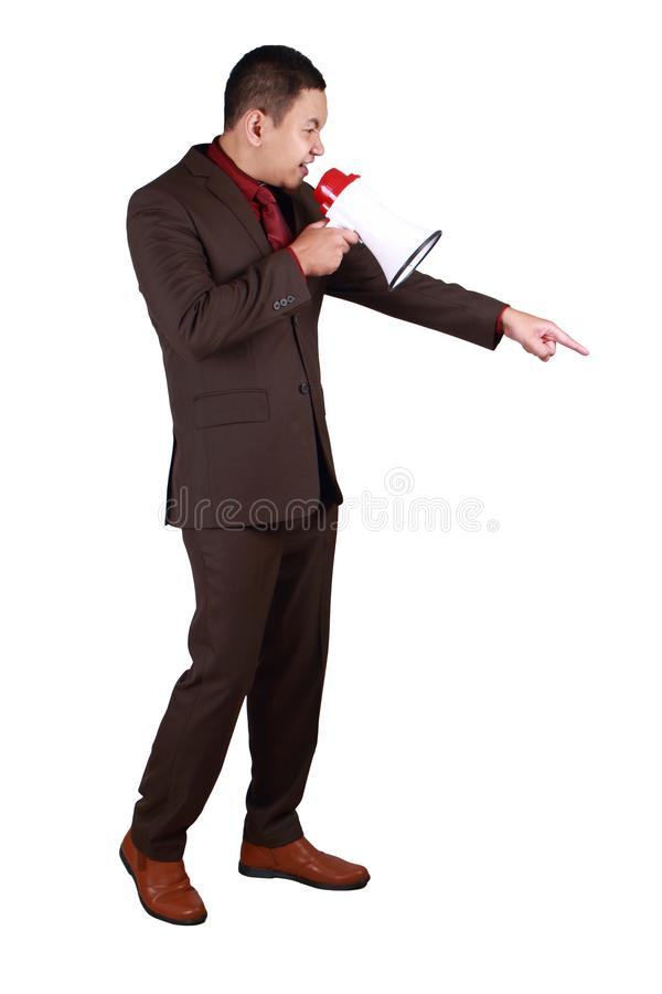Businessman Shout with Megaphone. Young Asian businessman wearing brown formal suit shout with megaphone, angry big boss giving instruction, side view full body royalty free stock images