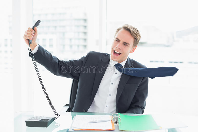 Download Businessman Shouting As He Holds Out Phone At Office Stock Photo - Image of half, length: 35029546