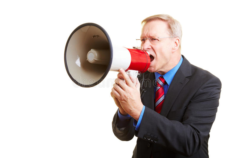 Businessman shouting with megaphone. Senior businessman screaming loudly in a big megaphone royalty free stock photos
