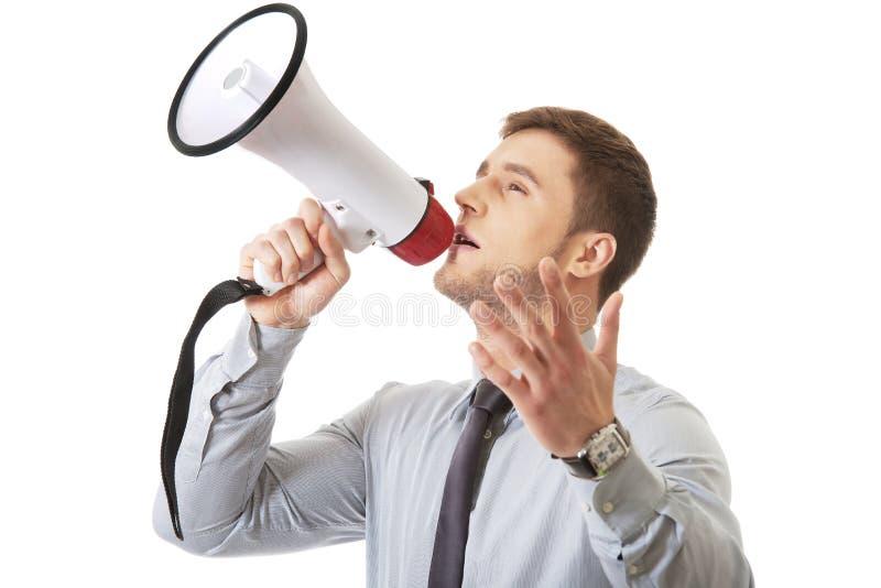 Businessman shouting through megaphone. royalty free stock photography
