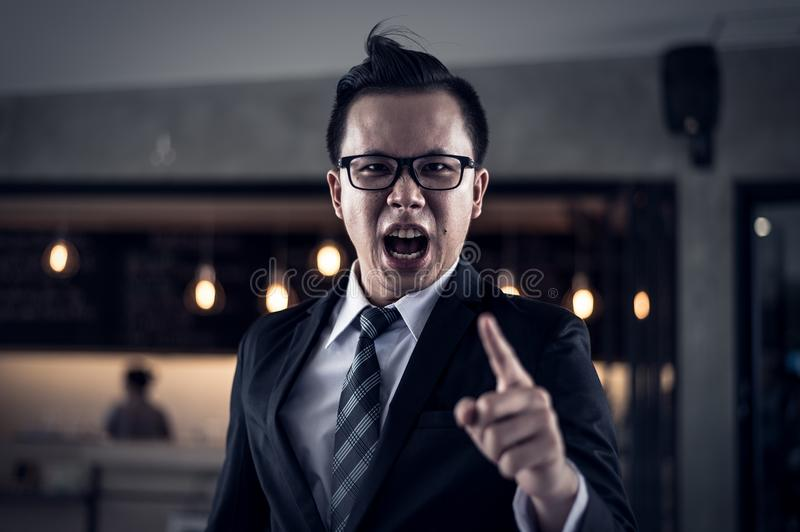Businessman shouting and pointing finger at you because he is very angry from financial reports decreased. Businessman shouting and pointing finger at you royalty free stock photography