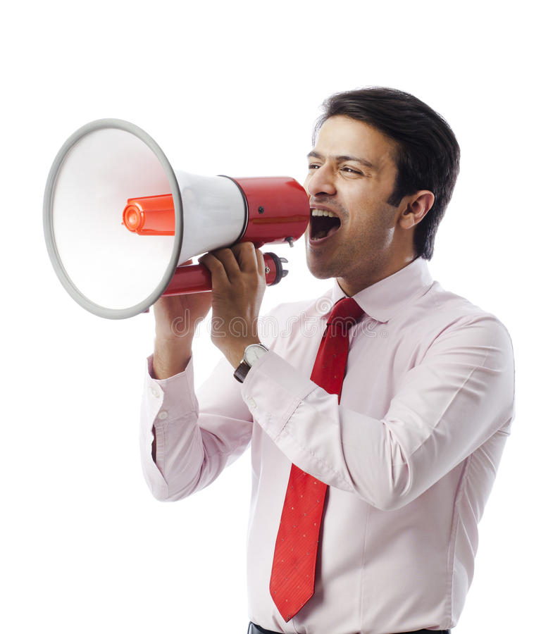 Businessman shouting on a speaker. Businessman shouting on a bullhorn royalty free stock images