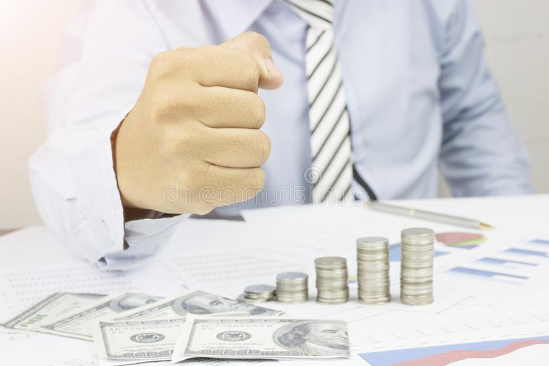 Businessman show fist to certain and success in business on table with money, work paper and coins, concept as be certain, confide royalty free stock image
