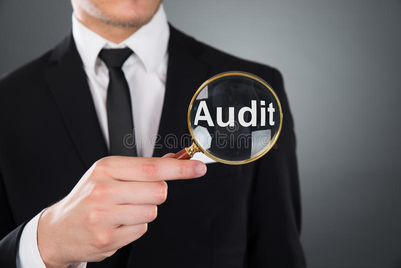 Businessman showing audit word through magnifying glass royalty free stock photos