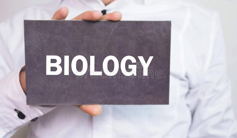 Businessman showing Biology word on cardboard. royalty free stock photography