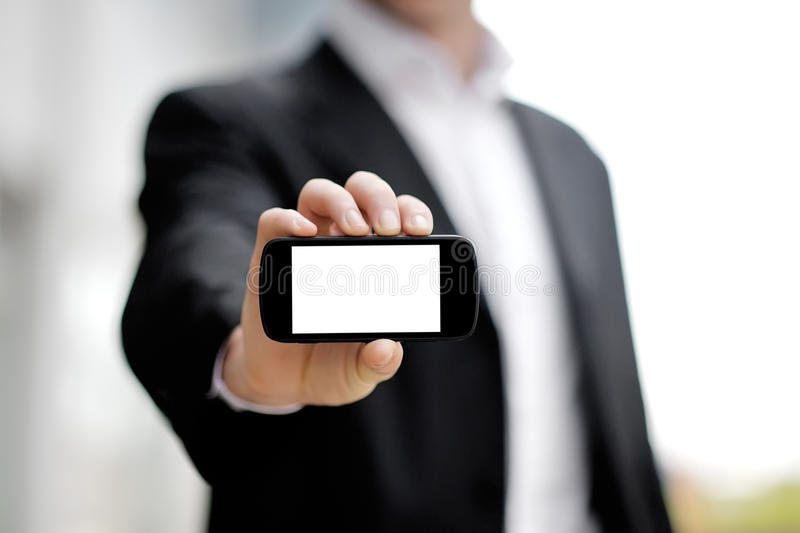 Businessman showing black mobile smart phone in hand. Businessman showing black mobile smart phone with white display in hand stock image