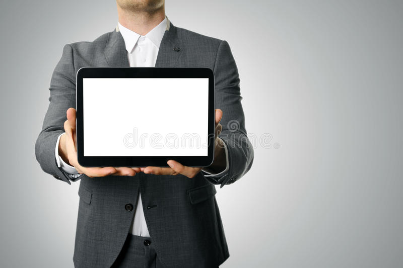 Businessman showing blank digital tablet. On gray background stock photo