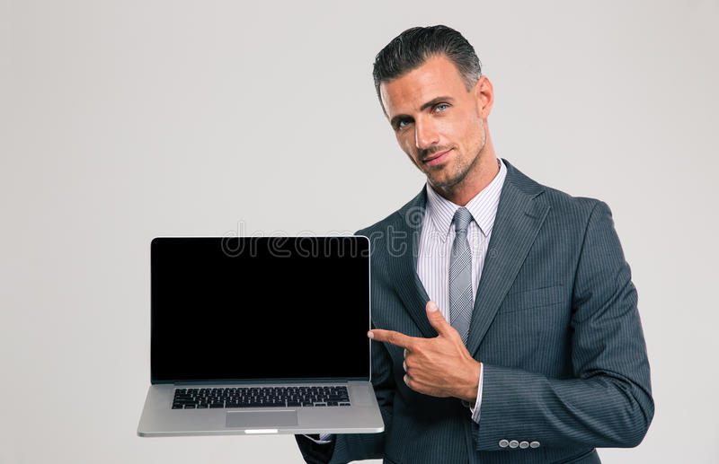 Businessman showing blank laptop computer screen. Portrait of a handsome businessman showing blank laptop computer screen isolated on a white background stock images