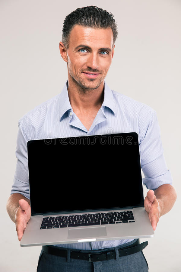 Businessman showing blank laptop computer screen. Portrait of a smiling handsome businessman showing blank laptop computer screen on a white background stock photography