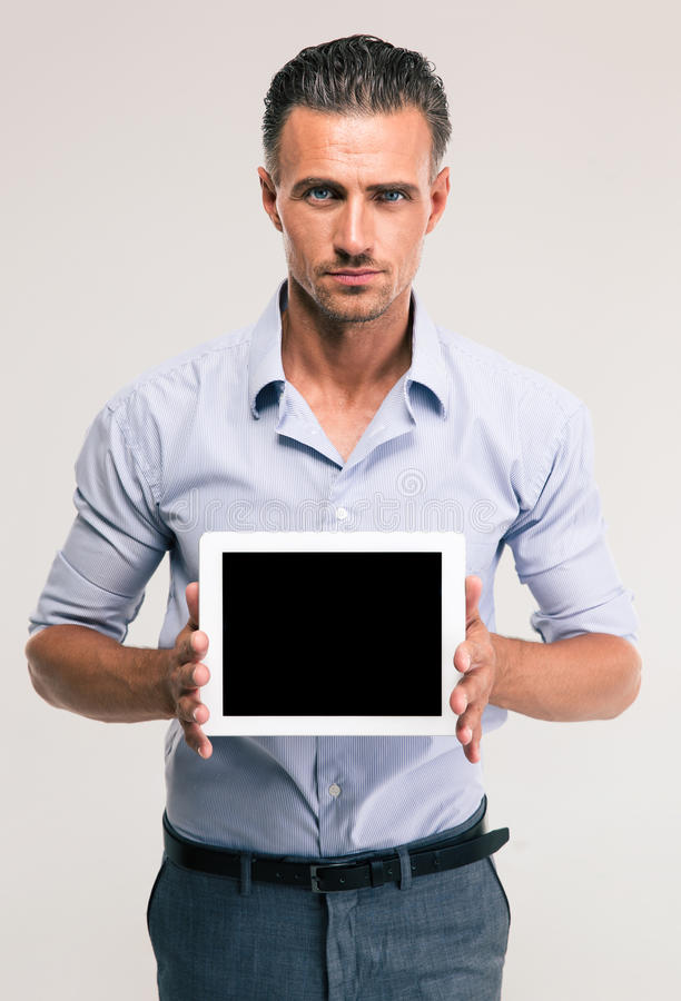Businessman showing blank tablet computer screen. Portrait of a handsome businessman showing blank tablet computer screen isolated on a white background royalty free stock photos