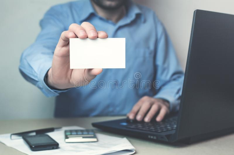 Businessman showing a business card in his business desk. royalty free stock images