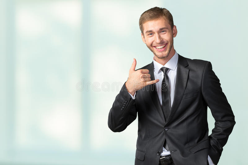 Businessman showing Call me sign. Young Businessman showing Call me sign stock image