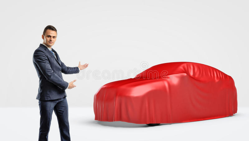 A businessman showing a car silhouette wrapped in a red cloth behind him. Shows and presentation. Automotive industry. Car dealership royalty free stock image