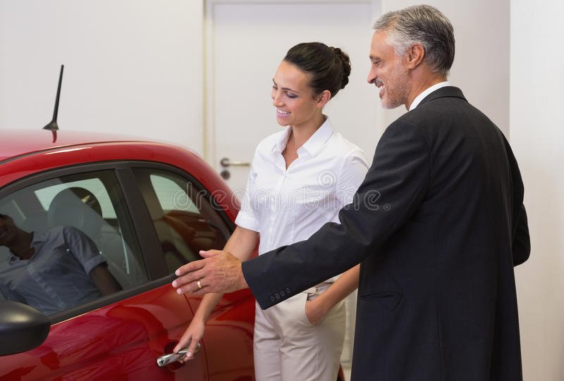 Businessman showing a car to a woman royalty free stock images