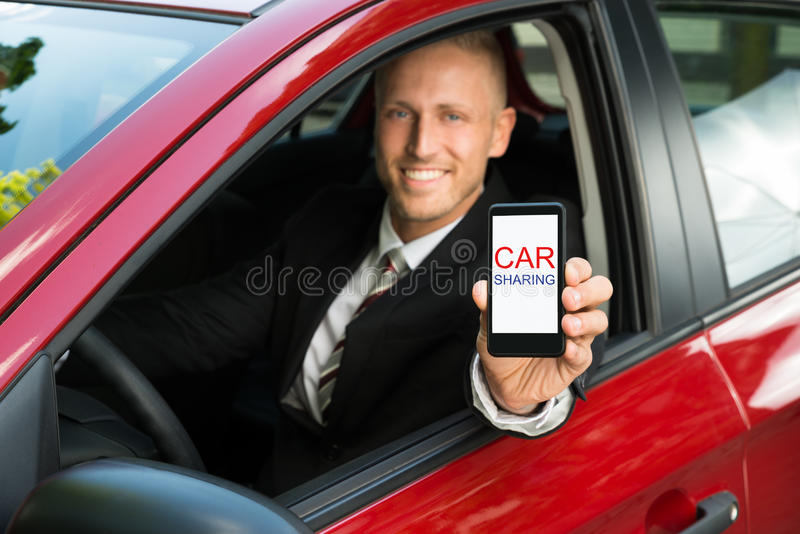 Businessman showing cellphone with car sharing text on screen stock photos