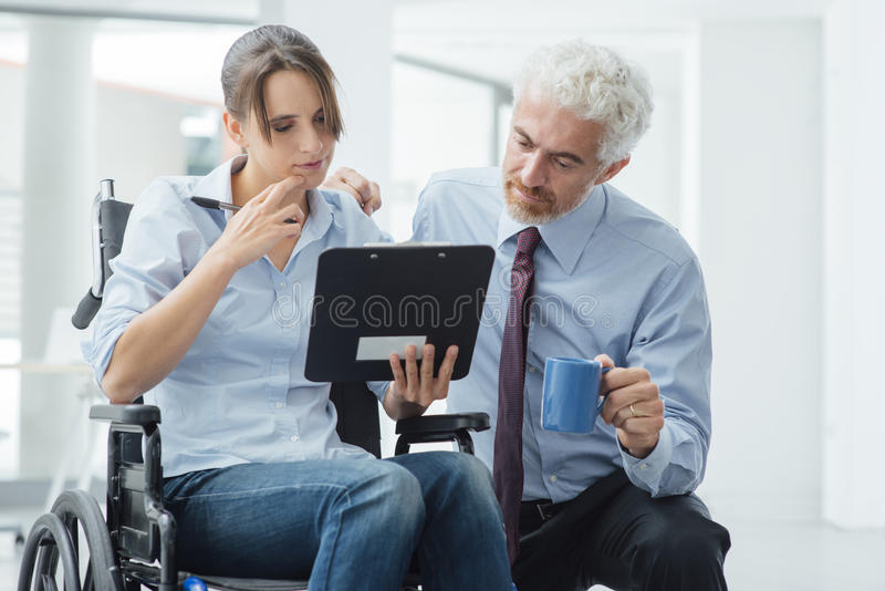 Businessman showing a document to a woman in wheelchair. Businessman showing a document on a clipboard to a young women in wheelchair, assistance and help stock photos