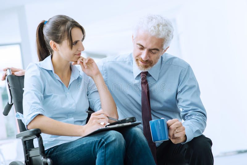 Businessman showing a document to a woman in wheelchair stock photo