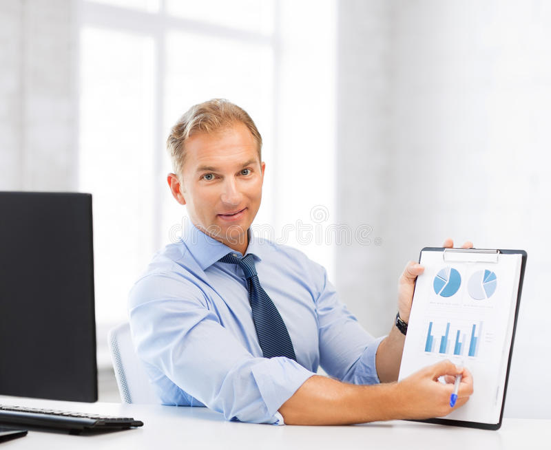Businessman showing graphs and charts. Picture of handsome businessman showing graphs and charts stock image