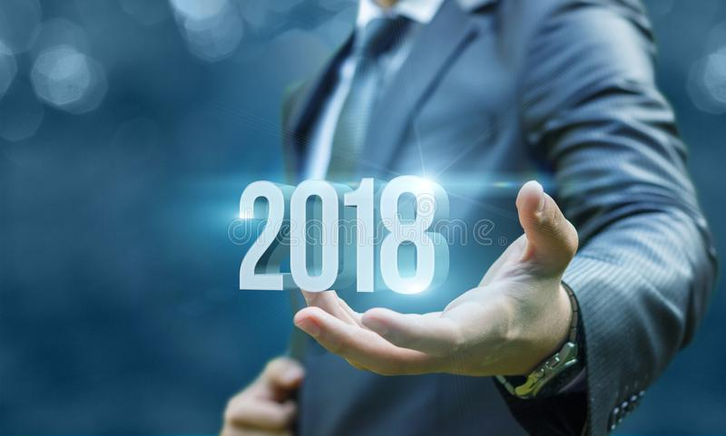 Businessman showing 2018 in hand . stock photos